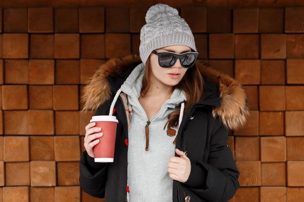 Mulher atraente jovem hippie no chapéu de malha com um moletom com uma jaqueta elegante em óculos de sol se passando perto de uma parede vintage de madeira e segurando uma xícara de café na mão. menina legal dia de inverno