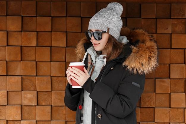Mulher atraente jovem hippie no chapéu vintage de malha em óculos de sol em uma jaqueta preta com um capuz de pele em um moletom elegante posa perto de uma parede de madeira ao ar livre. menina estilosa bebe chá quente