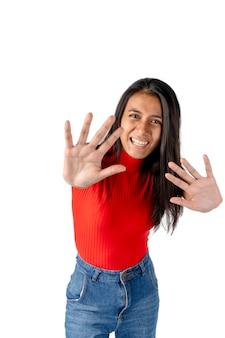 Mulher atraente latina de cabelos escuros com as mãos para a frente e uma expressão de medo no rosto em um fundo branco puro.