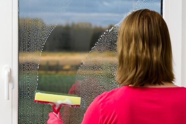 Mulher atraente, lavar uma janela com uma bela vista do campo