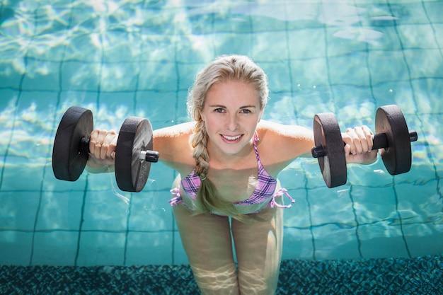 Mulher atraente levantando halteres na piscina