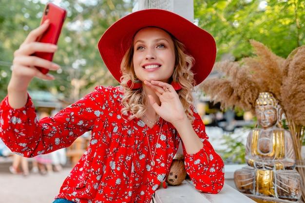 Mulher atraente loira elegante e sorridente com chapéu de palha vermelho e blusa, roupa da moda de verão, tirando foto de selfie na câmera do telefone inteligente
