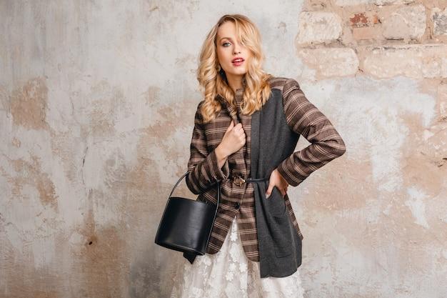 Mulher atraente loira elegante e sorridente com jaqueta quadriculada caminhando contra a parede na rua