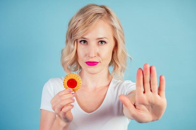 Mulher atraente loira triste com maquiagem e lábios cor fúcsia segurar um biscoito de alto teor calórico no estúdio sobre um fundo azul. conceito de dieta e rejeição (parada) de produtos de farinha