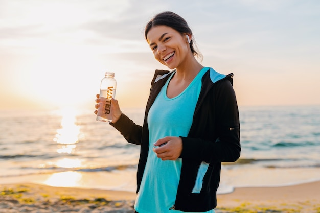 Mulher atraente magro fazendo exercícios de esporte na praia ao nascer do sol de manhã em roupas esportivas, água potável na garrafa com sede, estilo de vida saudável, ouvindo música em fones de ouvido sem fio, sorrindo feliz