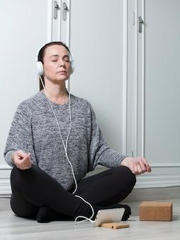Mulher atraente mais velha praticando ioga com fones de ouvido