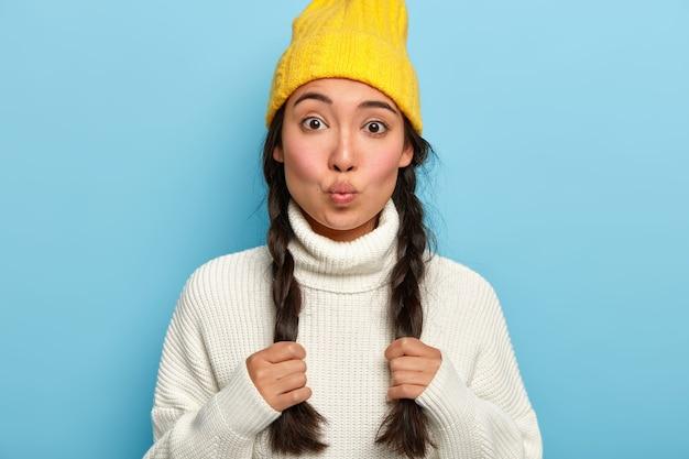 Mulher atraente mantém os lábios arredondados, segura duas marias-chiquinhas, vestida de suéter branco quente e chapéu amarelo, tem olhar glamour para a câmera, isolada sobre paredes azuis