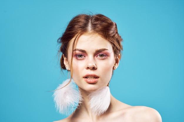 Mulher atraente maquiagem brilhante brincos joias ombros nus azuis.