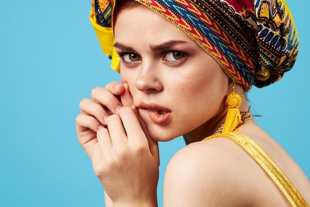 Mulher atraente maquiagem brilhante etnia decoração turbante multicolorido estúdio azul