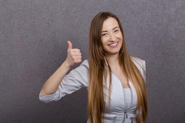 Mulher atraente médico feminino mostra os polegares para cima