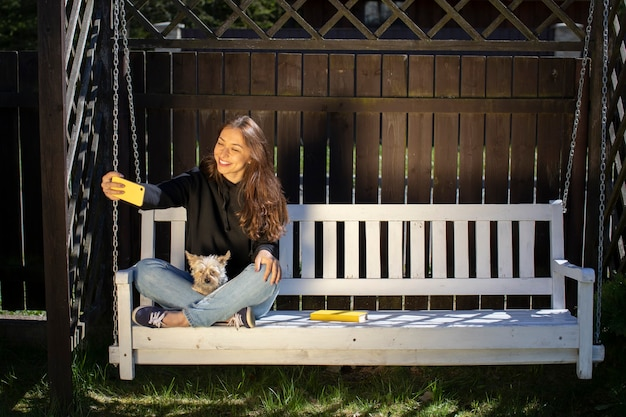 Mulher atraente morena com cabelo comprido, vestida com um capuz preto e fazendo selfies no banco de balanço branco com um cachorro yorkshire