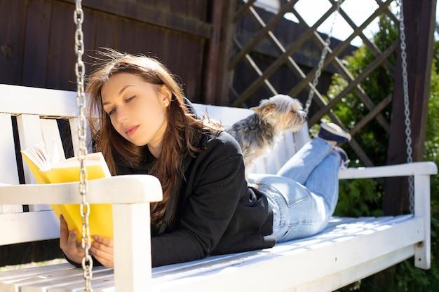 Mulher atraente morena com cabelos longos, vestida com um capuz preto deitada no banco de balanço branco lendo livro com cachorro yorkshire