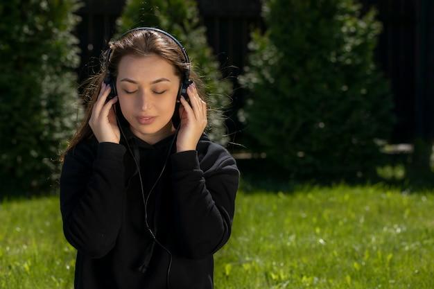 Mulher atraente morena de cabelos longos, vestida com um capuz preto, ouvindo música com fones de ouvido, sentada na grama