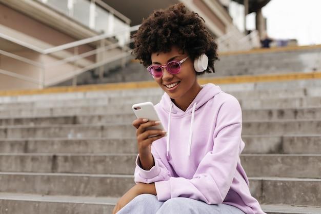 Mulher atraente morena encaracolada com capuz roxo e óculos de sol rosa sorri, segura o telefone, ouve música em fones de ouvido e senta-se na escada ao ar livre