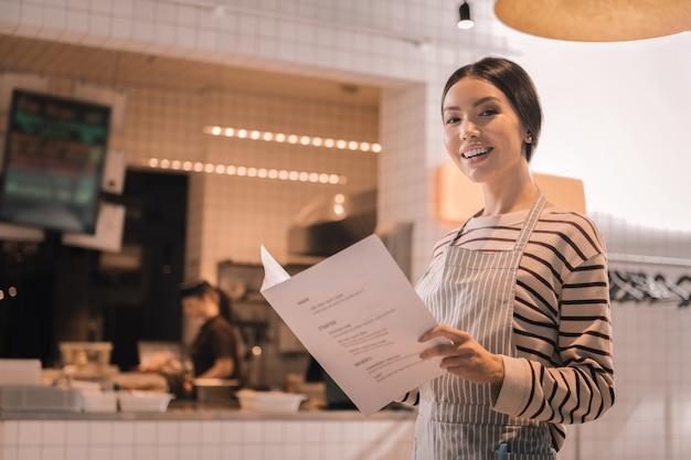 Mulher atraente. mulher bonita e atraente sorrindo amplamente enquanto segura o cardápio de seu restaurante