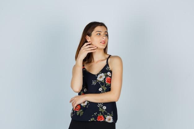 Mulher atraente na blusa, tocando sua bochecha e olhando encantadora, vista frontal.