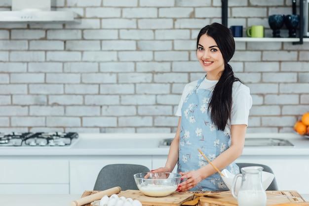 Mulher atraente na cozinha estará cozinhando comer comida saudável