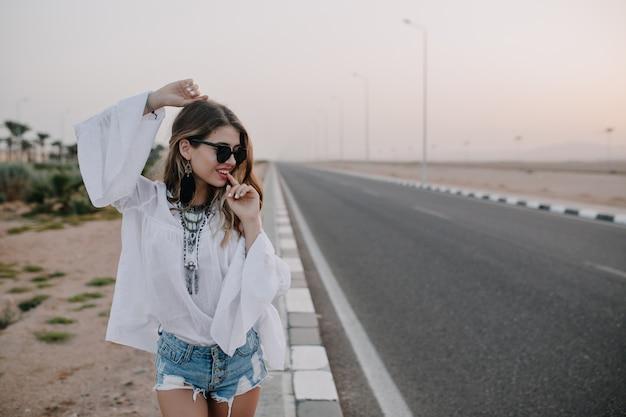 Mulher atraente na moda dançando com as mãos ao alto, perto da rodovia e gosta de noite de verão. adorável jovem sorridente, usando óculos escuros pretos e shorts jeans, posando alegremente perto da estrada ao pôr do sol