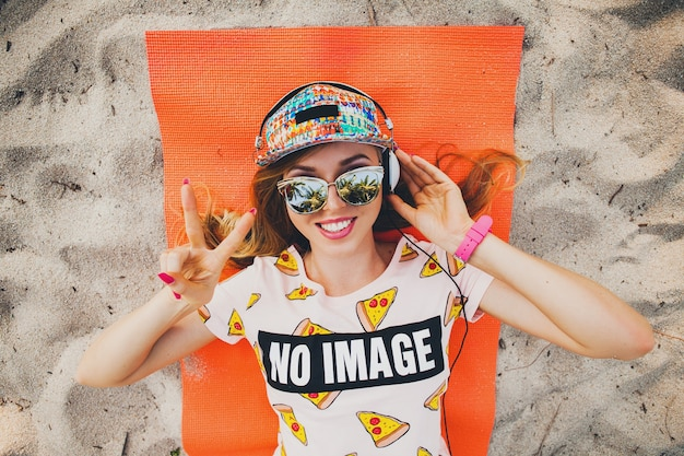 Mulher atraente na praia, ouvindo música em fones de ouvido, com roupa colorida elegante nas férias de verão tropical usando acessórios de boné de óculos escuros, sorrindo feliz deitada na esteira de ioga vista de cima