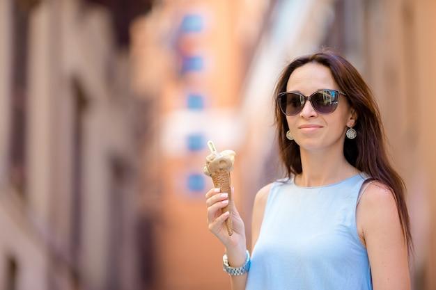 Mulher atraente na rua se divertindo e comendo sorvete.