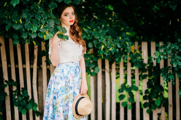 Mulher atraente na saia longa retrô vintage, top branco antiquado e cabelo ruivo cacheado e chapéu de palha posando ao ar livre
