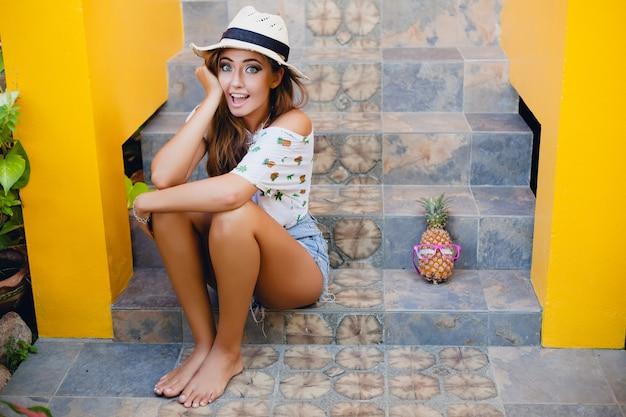 Mulher atraente nas férias de verão com expressão engraçada sorrindo emocional usando chapéu de palha sentada descalça surpresa