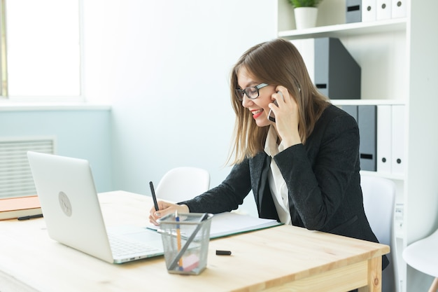 Mulher atraente no escritório falando ao telefone e fazendo anotações