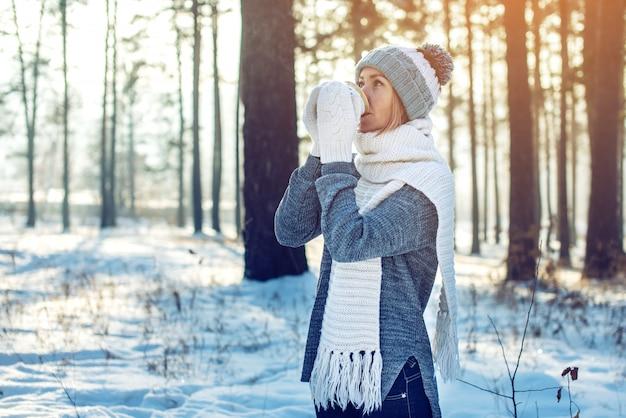 Mulher atraente no inverno, bebendo chá quente na luz solar