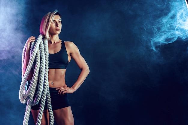 Mulher atraente no sportswear preto com cordas pesadas nos ombros na parede escura. força e motivação. desportiva mulher trabalhando com cordas pesadas.