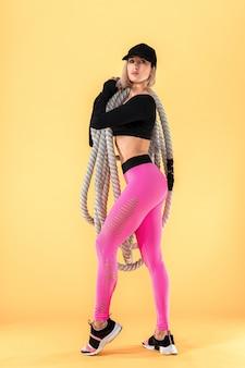 Mulher atraente no sportswear rosa e preto com cordas pesadas, olhando para a câmera na parede amarela. força e motivação. desportiva mulher trabalhando com cordas pesadas.