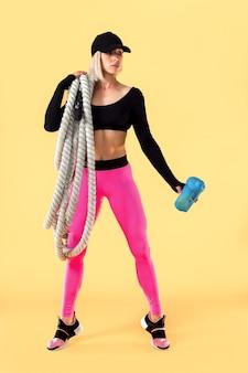 Mulher atraente no sportswear rosa e preto com cordas pesadas sobre os ombros e segurando o abanador na parede amarela. força e motivação. desportiva mulher trabalhando com cordas pesadas.