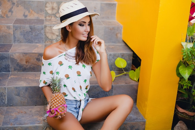 Mulher atraente no verão, sorrindo, usando um chapéu de palha, sentada descalça em uma camiseta impressa, férias da moda