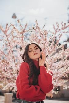 Mulher atraente num suéter brilhante olha para a câmera no fundo de sakura. foto de uma senhora de suéter vermelho posando do lado de fora e curtindo a primavera