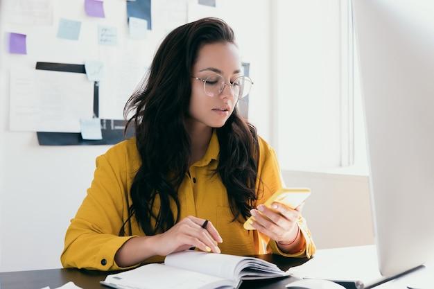 Mulher atraente ocupada de óculos redondos pesquisando informações na web ou respondendo ao cliente pelo smatphone