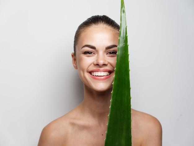 Mulher atraente olha para uma folha verde diante de seus olhos e sorri em um fundo claro