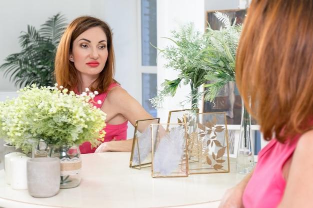 Mulher atraente olha tristemente para seu reflexo no espelho mulher pensa sobre sua idade
