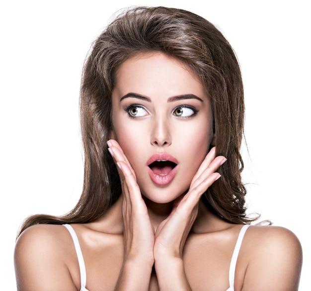 Mulher atraente olhando de soslaio. jovem surpreendida de empolgação.