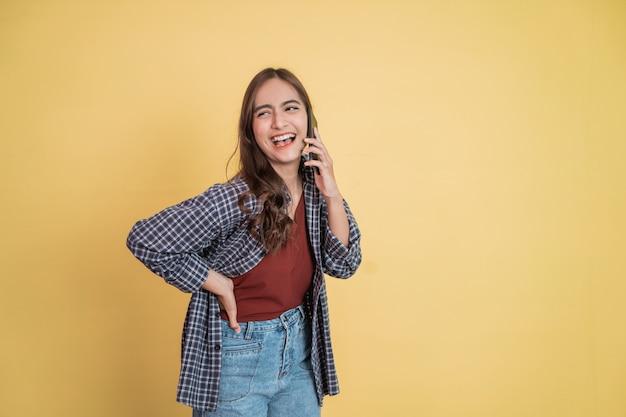 Mulher atraente ouvindo uma chamada usando um telefone celular e rindo alegremente com copyspace