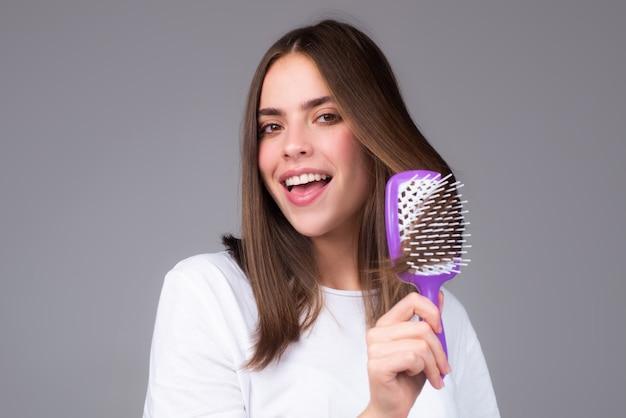 Mulher atraente penteando o cabelo. linda garota com pente de cabelo penteia o cabelo. conceito de cuidados com os cabelos.