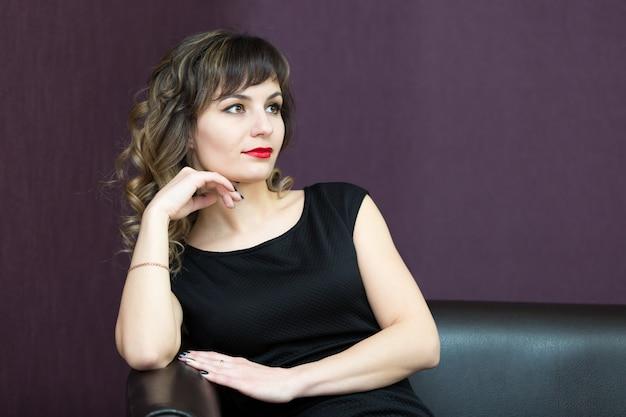Mulher atraente, posando de vestido preto