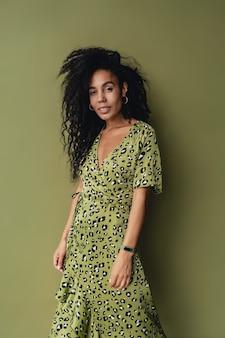 Mulher atraente posando em um elegante vestido estampado de leopardo verde isolado na parede verde do estúdio
