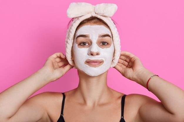 Mulher atraente posando isolado sobre o fundo rosa do estúdio, olhando diretamente para a câmera, mantendo as mãos na fita para a cabeça, carrinhos com máscara hidratante.