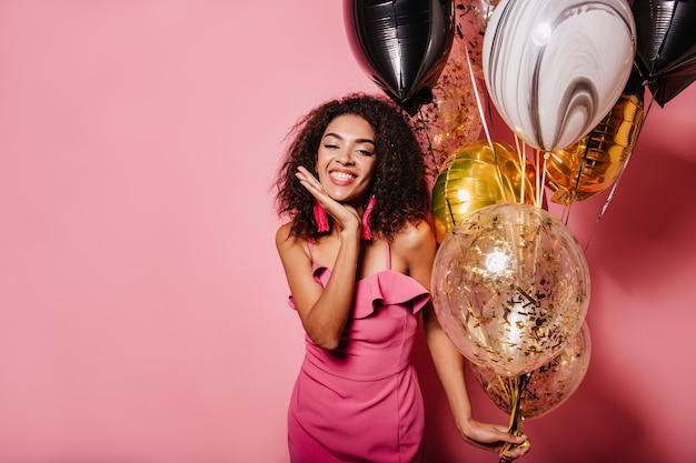 Mulher atraente posando na parede rosa com um sorriso