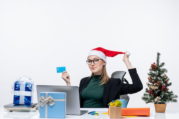 Mulher atraente positiva brincando com seu chapéu de papai noel e usando óculos, sentado à mesa e segurando um cartão do banco no escritório
