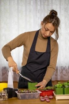 Mulher atraente positiva e alegre plantando plantas em vasos com pá interna