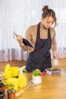 Mulher atraente positiva e alegre segurando um diário, plantando plantas em vasos internos