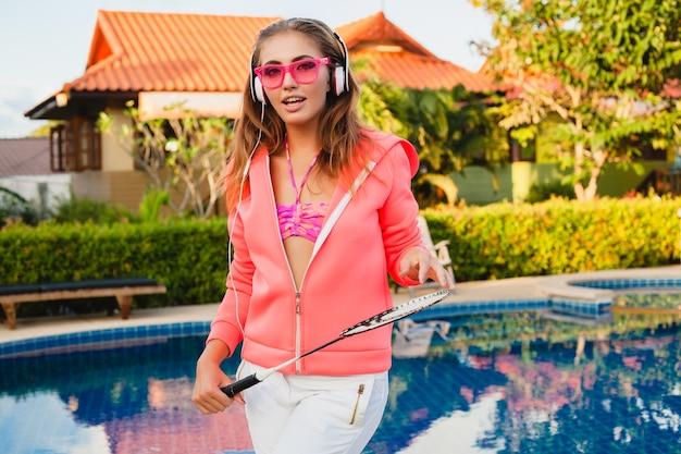Mulher atraente praticando esportes na piscina com capuz rosa colorido com óculos escuros, ouvindo música em fones de ouvido nas férias de verão, jogar tênis, estilo esportivo
