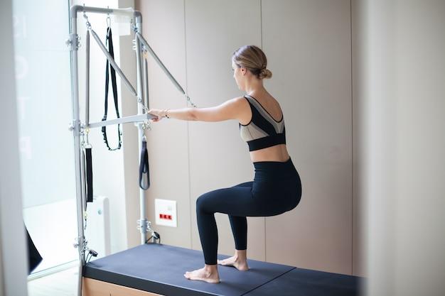 Mulher atraente praticando pilates em cama reformadora