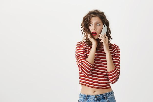 Mulher atraente preocupada e chocada reage a más notícias por telefone