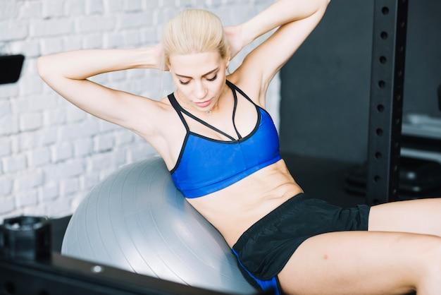 Mulher atraente que faz exercícios abs em fitball